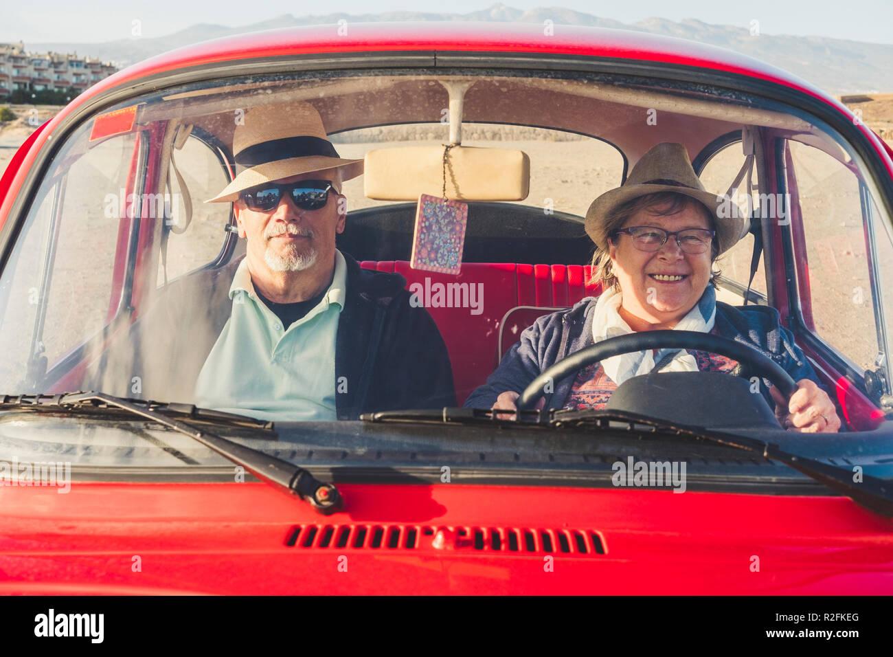 Hombre y mujer senior con sombreros divertirse en el verano dentro de un viejo coche rojo. Ella siles y él es grave con gafas de sol. Jóvenes positivos antiguo concepto. Imagen De Stock