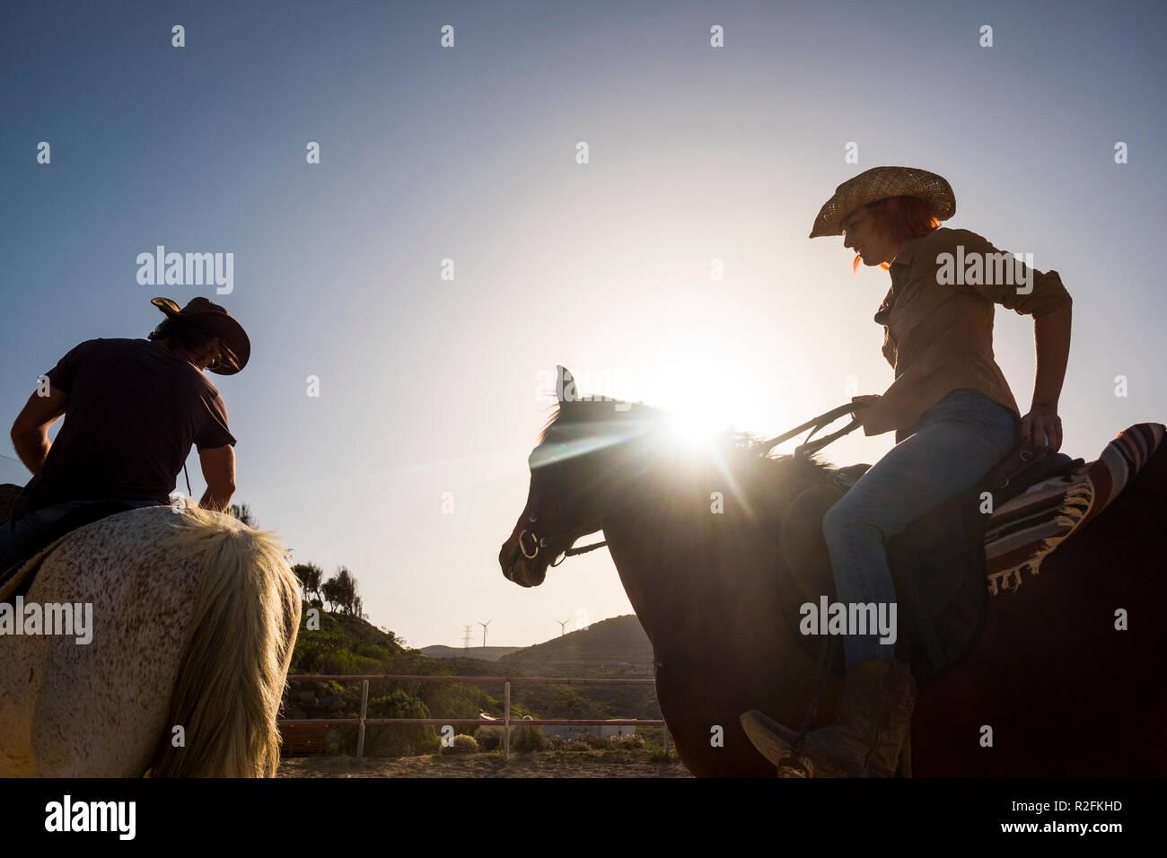 Par de vaqueros modernos hombre y mujer montar dos caballos y sunflare exterior con retroiluminación. montañas y molino de viento de fondo. hermosa joven de vacaciones Foto de stock