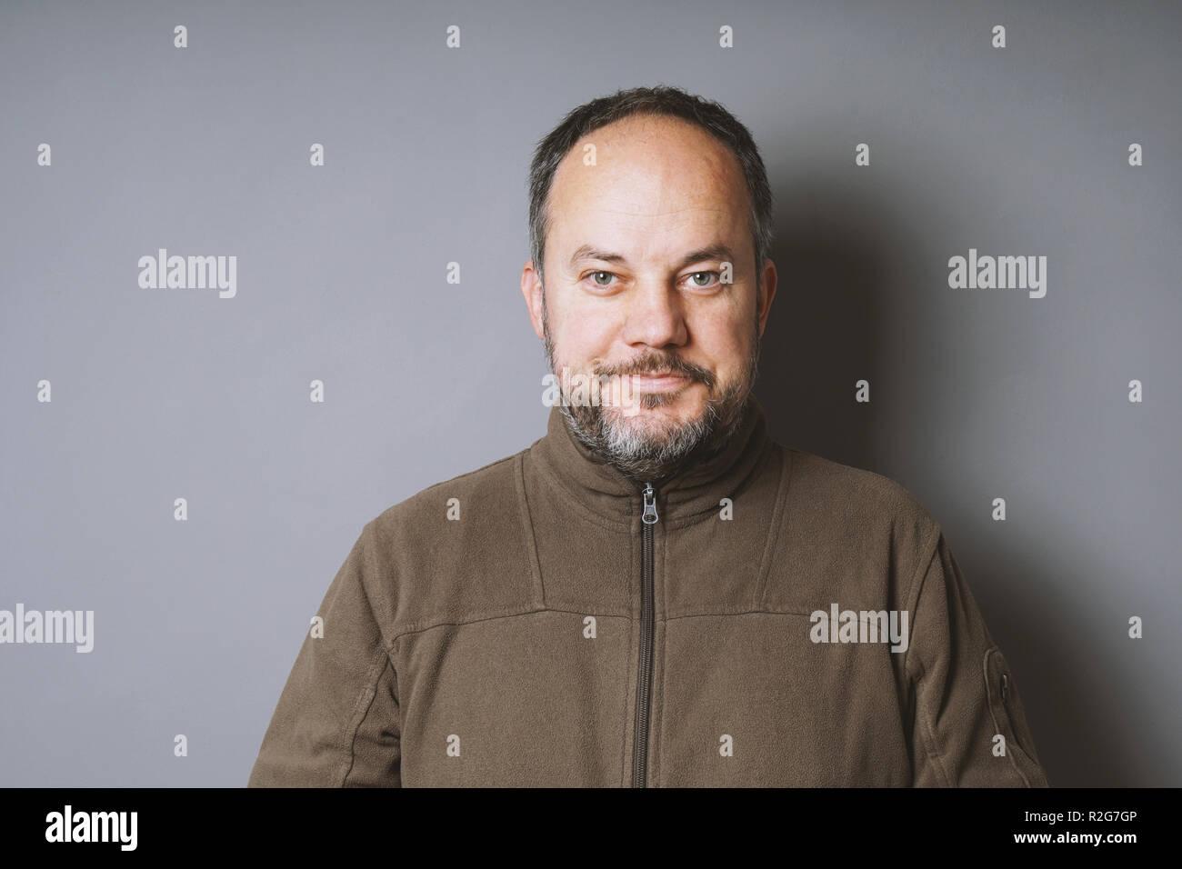 Un varón de mediana edad en su 40s con el cabello oscuro corto y encanecimiento barba sonriente contra la pared gris con espacio de copia Imagen De Stock