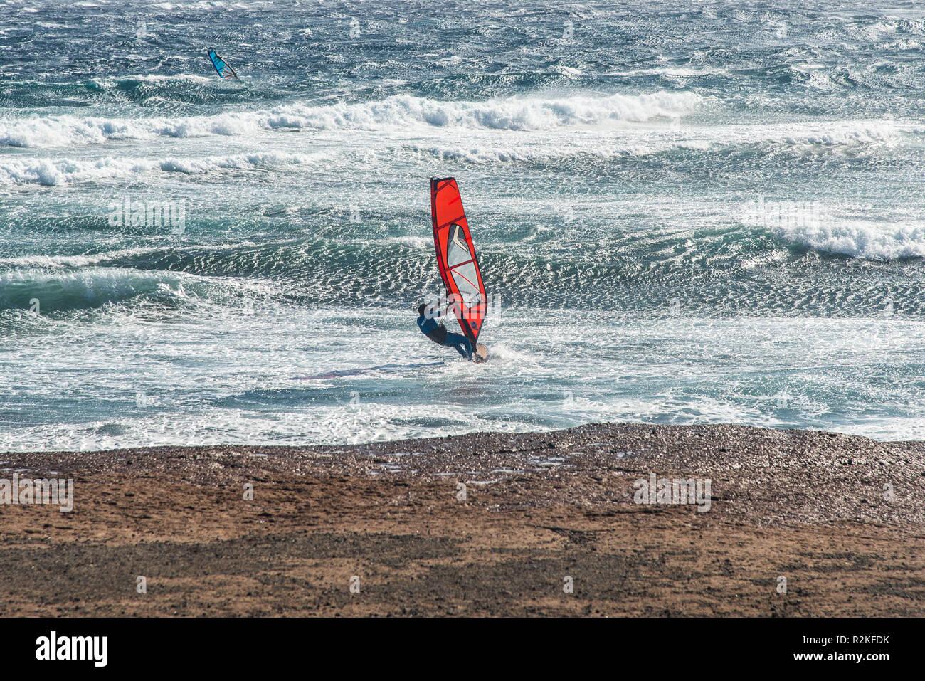 Una tabla de windsurf con red navegar con viento fuerte surfeando en un fuerte oleaje. Imagen De Stock