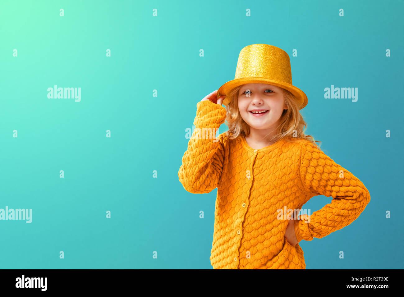 Retrato de una niña en una chaqueta tejida de mostaza y un cilindro amarillo  brillante sombrero 5d02562f31e