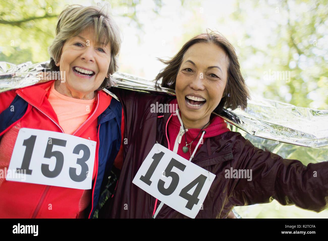 Retrato sonriente, seguro activo mujeres senior acabado la carrera deportiva, envuelto en una manta térmica Imagen De Stock
