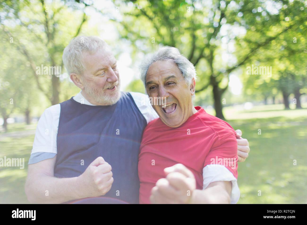Activa exuberante altos hombres amigos vitoreando en estacionamiento Imagen De Stock