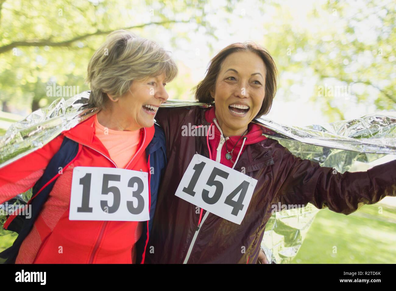Feliz mujeres senior activo acabado la carrera deportiva, envuelto en una manta térmica Imagen De Stock