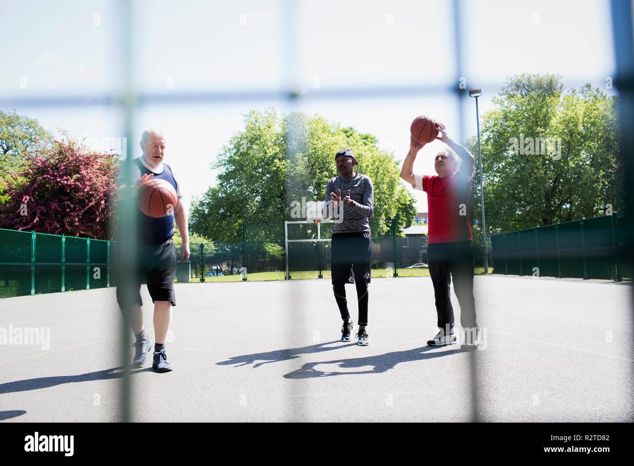 Active altos hombres jugando básquetbol en sunny park Foto de stock