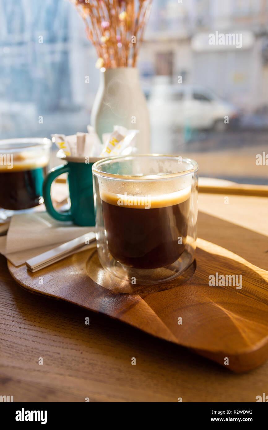 Por la mañana Una taza de delicioso sabor americano en una mesa de madera cerca de la ventana panorámica Imagen De Stock