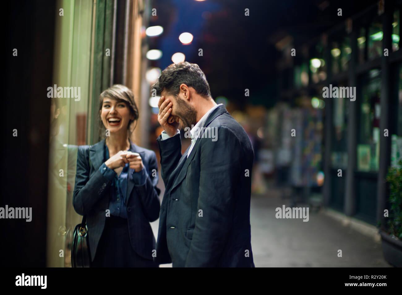 Joven se siente avergonzado por algo que acaba de decir mientras una fecha después del trabajo con un colega. Foto de stock