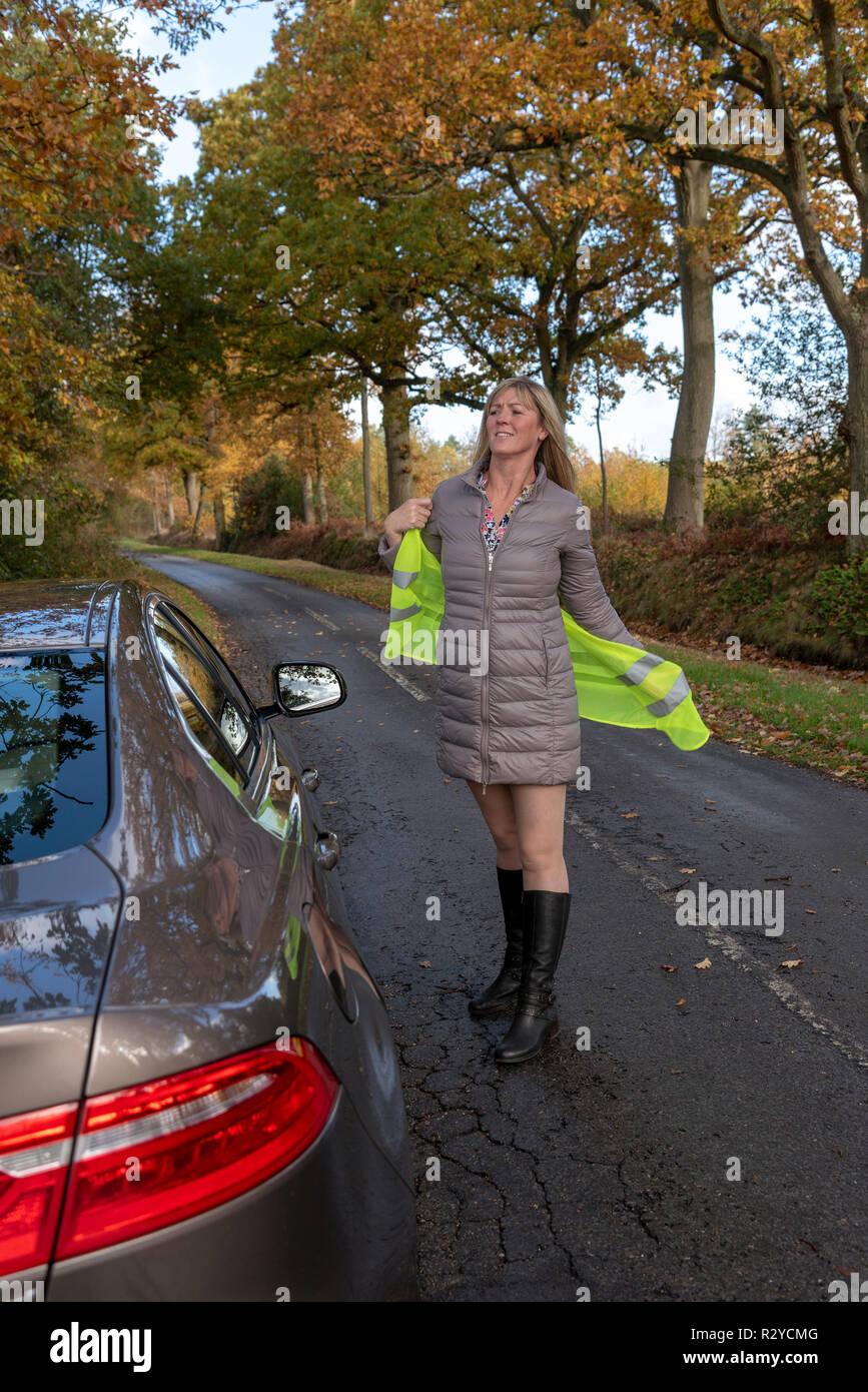 Mujer automovilista por su coche poniendo en una chaqueta de seguridad reflectantes Foto de stock
