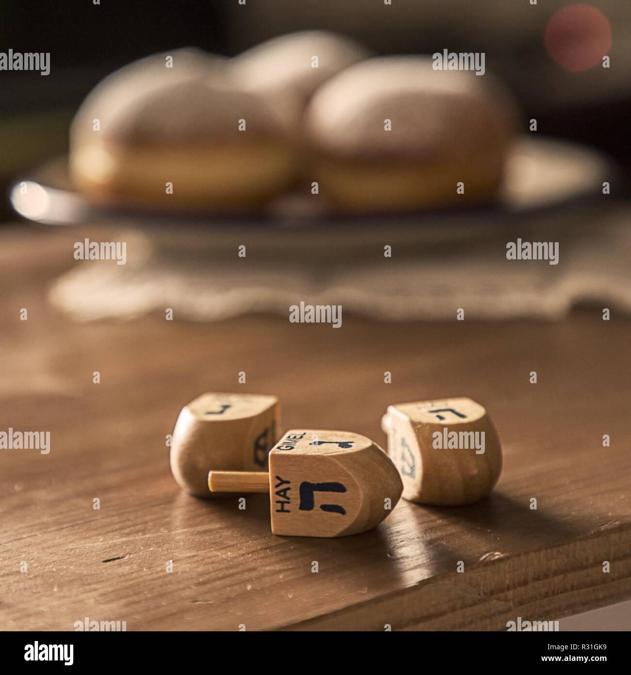 Still life para la fiesta judía de Hanukkah con celebración de Jánuca Concepto-dreidels sobre la rústica mesa con Donuts en segundo plano. Retroiluminación de la ventana.Shal Foto de stock