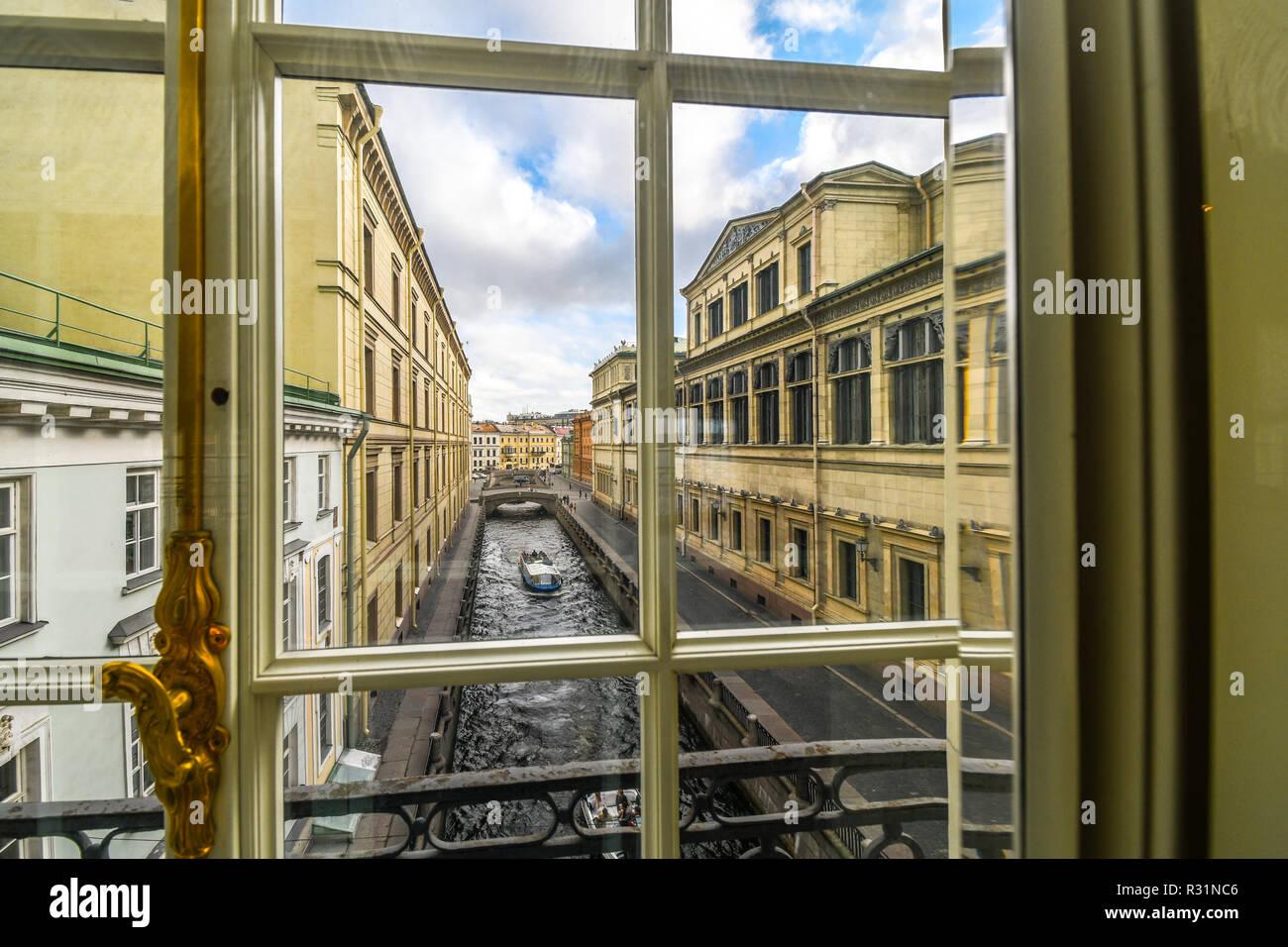 Un barco se desliza hacia abajo el invierno Kanavka Zimnyaya Canal y el río Neva en San Petersburgo, Rusia, vista desde una ventana de la galería en el interior de la Ermita Foto de stock