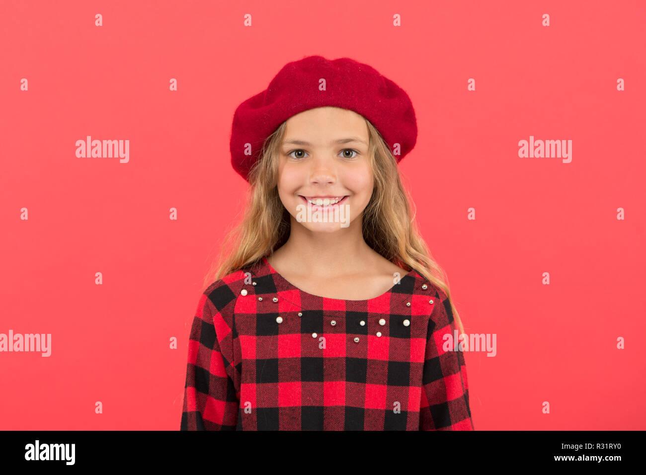 Cómo boina de desgaste como chica de moda. Niño Niña con cabello largo  posando en el sombrero y vestido a cuadros sobre fondo rojo. Boina moda  sombrero para ... f5dfd29f711