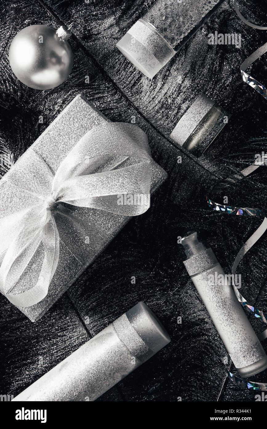 Vista elevada de bola, caja de regalo de navidad y el equipo de tratamiento de belleza en la superficie con plumas negras cubierto por Silver Foto de stock