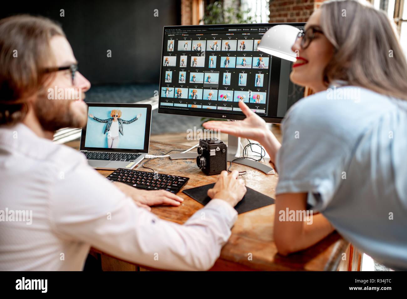 Pareja joven de fotógrafos que trabajan con retratos de la mujer en el lugar de trabajo con dos ordenadores en el studio Foto de stock