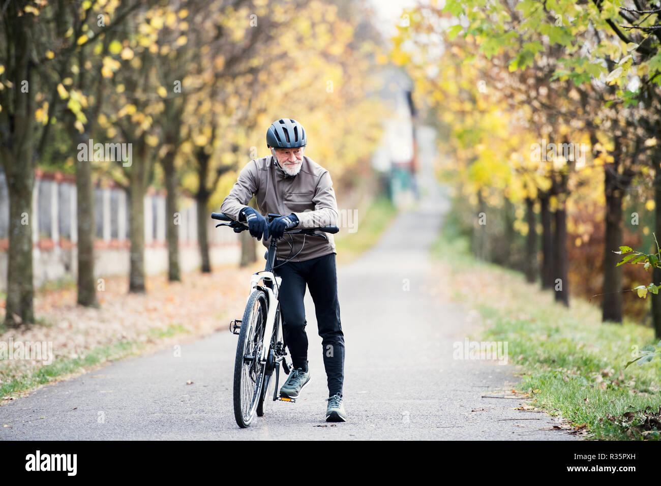 Hombre con electrobike senior activo de pie afuera en una carretera en la naturaleza. Foto de stock