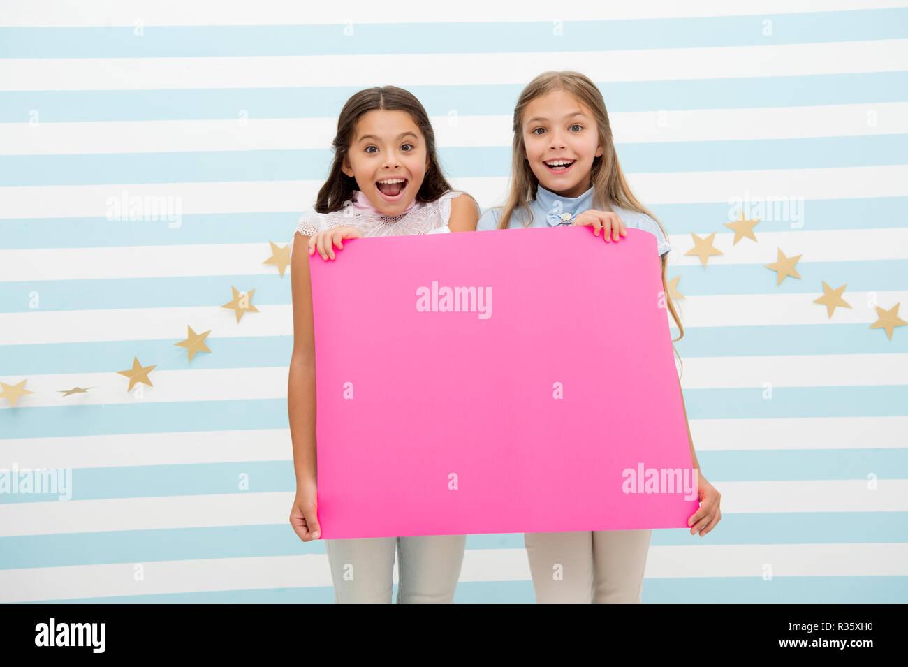 Increíble noticia sorprendente. Chica mantenga anuncio banner. Las niñas niños sosteniendo pancartas de papel para el anuncio. Los niños felices con el papel en blanco el espacio de copia de anuncio. Concepto de anuncio para niños. Imagen De Stock