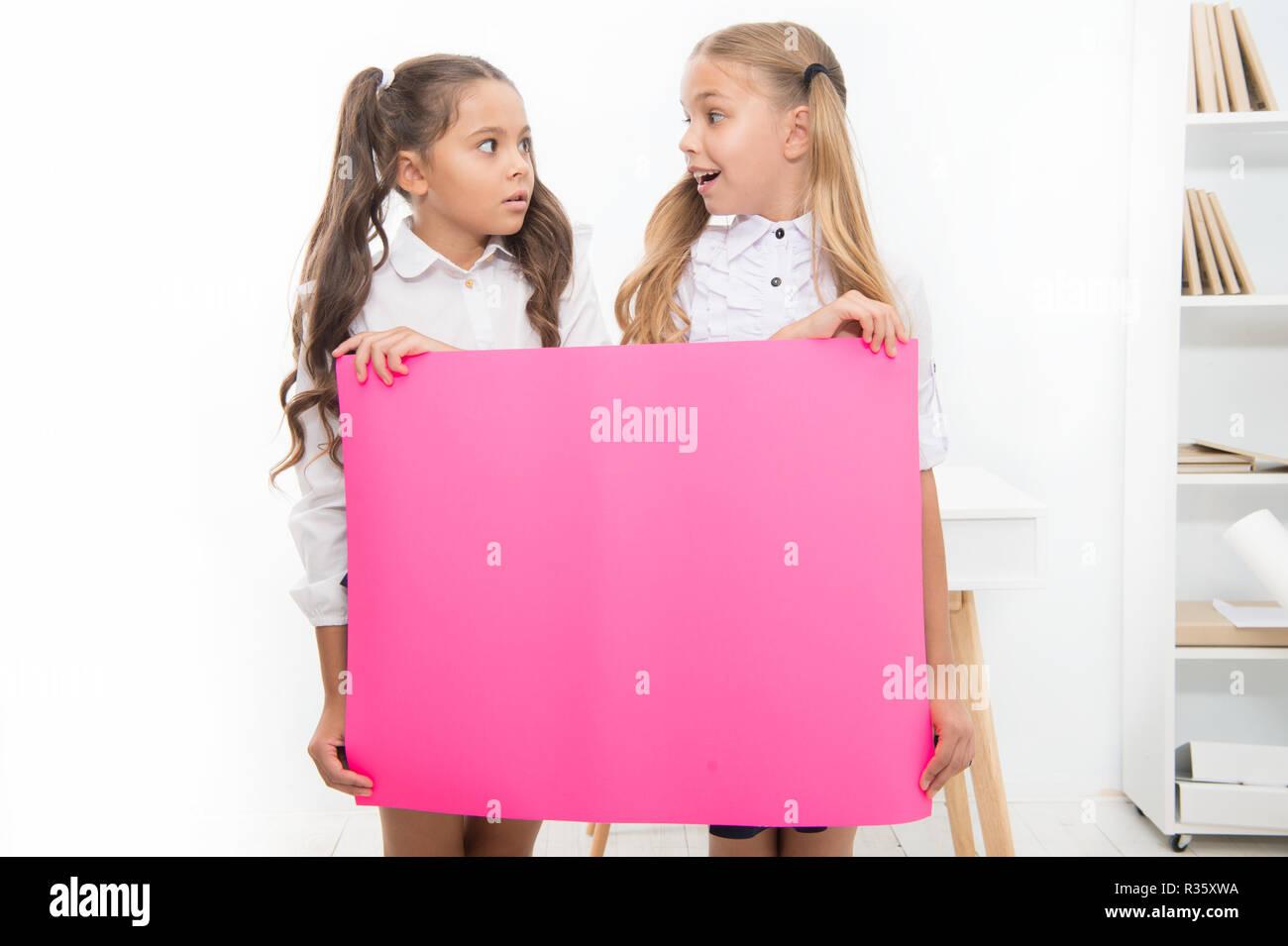 Anuncio de escuela concepto. Sorprendente noticia. Las niñas mantenga anuncio banner. Las niñas niños sosteniendo pancartas de papel para el anuncio. Los niños sorprendidos con papel en blanco escuela espacio de copia de anuncio. Imagen De Stock