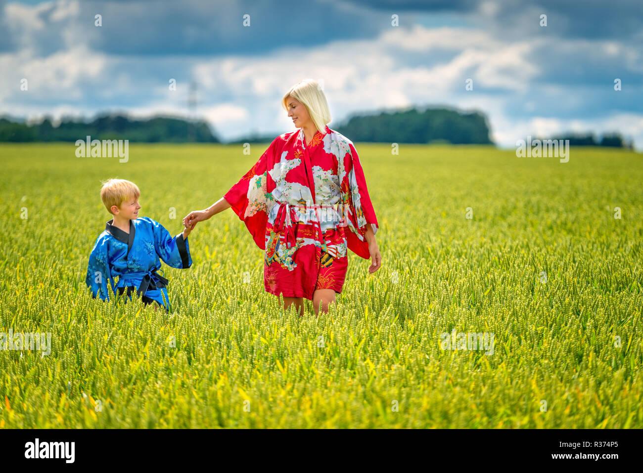 Mujer rubia y el muchacho, vestida en kimono, vaya a través del campo de cultivo Fotografía de stock - Alamy