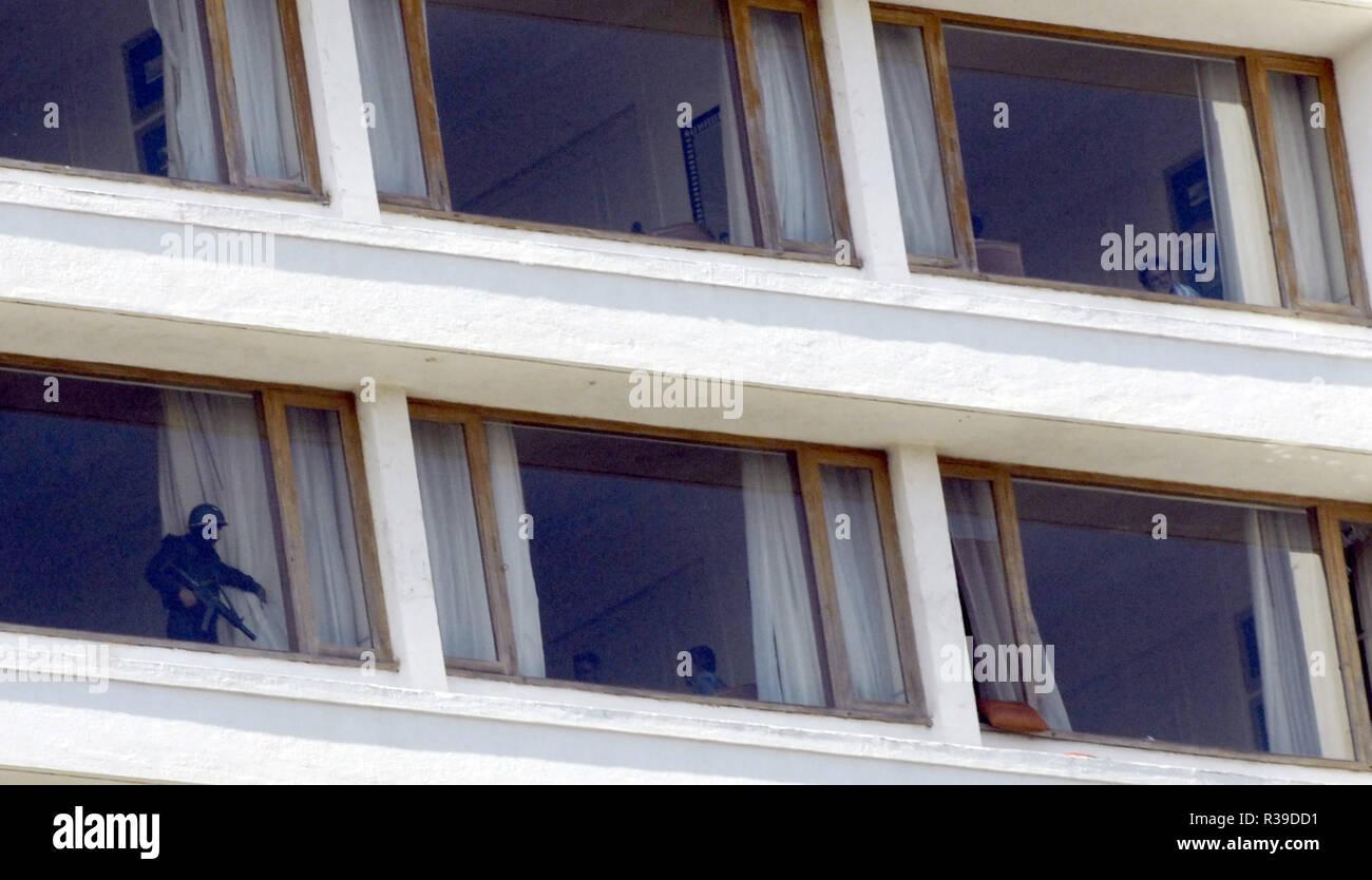 Guardia de Seguridad Nacional NSG commando abriendo la cortina para indicar la habitación está a salvo de Deccan Muyahidín terroristas en Oberoi Hotel Trident Nariman Point Mumbai, India el 27 /11/2008. Los terroristas mataron a 100 personas y más de 200 heridos en una serie de ataques coordinados a través de la India?s del centro financiero de Mumbai como pistoleros fuertemente armados en grupos de dos a cuatro abrieron fuego con armas automáticas y granadas lobbed en 10 lugares en el sur de Mumbai, incluidos los cinco estrellas hoteles Taj y Trident, la ciudad?s terminal principal de trenes, un hospital, una cafetería, un pub y una sala de cine. Foto: Dinodia (c) dpa - Report Foto de stock