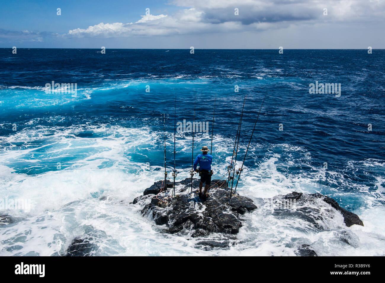 Pescador de pie sobre una roca en el mar con sus varillas laterales, Kalae, South Point, Big Island, Hawaii, EE.UU. Imagen De Stock