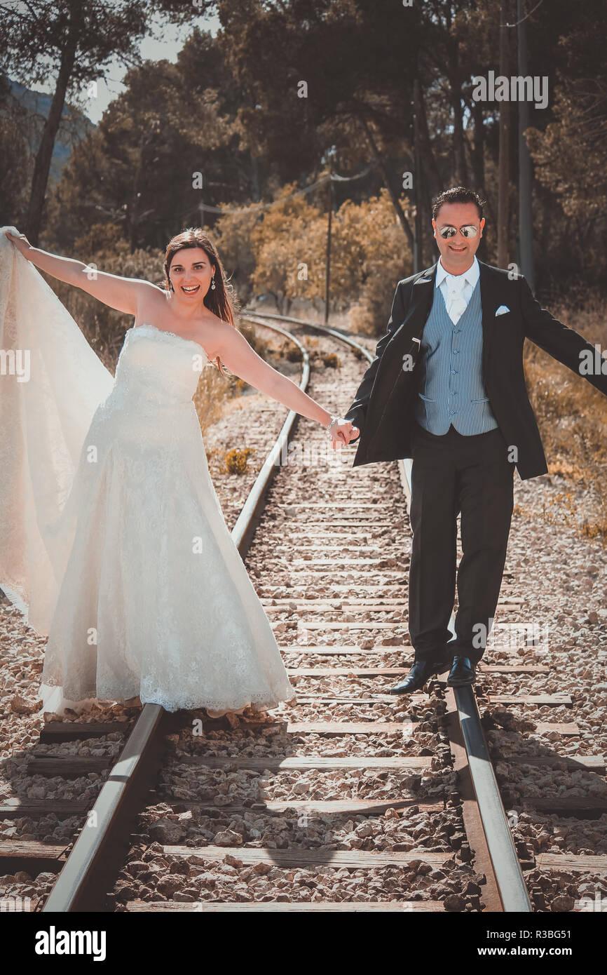 Pareja de recién casados caminando sobre un ferrocarril Imagen De Stock