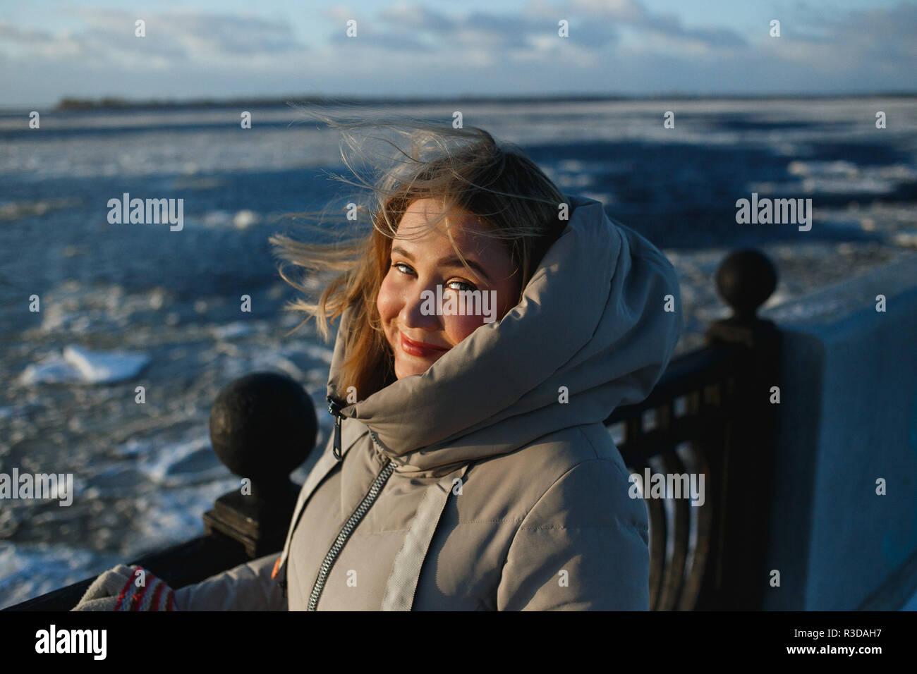 Retrato de bastante alegre mujer sonriente en el fondo del río congelado en el soleado día de invierno. Caminar en invierno saludable sinny frosty día. Imagen De Stock
