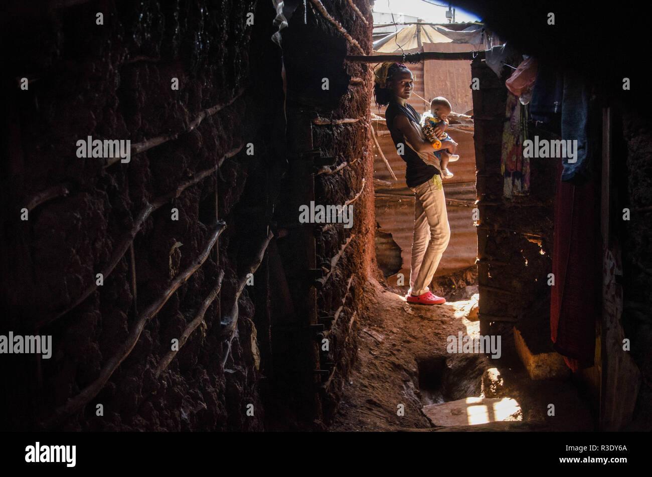 Una mujer visto cargando un niño en el bar local. Durante un largo período de tiempo, la mayoría de las mujeres de Kibera han sido los barrios bajo la influencia del alcohol. No considerar los efectos secundarios, aquí las mujeres consumen por diferentes razones, incluyendo la toma de más estrés y olvidarse de sus problemas familiares de regreso a casa. Esto es debido a la falta de suficientes oportunidades de empleo y el apoyo de sus maridos, el alto nivel de consumo de alcohol ha llevado a la mayor tasa de muertes, ceguera y riesgo de muchas enfermedades peligrosas como el cáncer, la hipertensión, apoplejía y lesiones traumáticas con niños dejados como Orpha Foto de stock