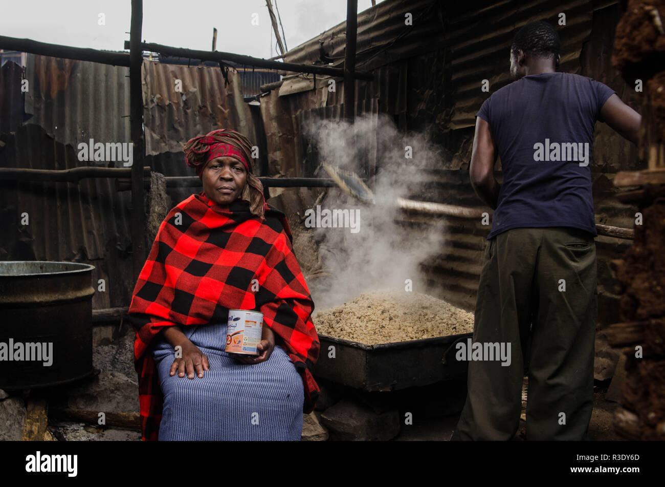 Un hombre es visto asar mezcla de sorgo con el fin de preparar el alcohol en Kibera. Durante un largo período de tiempo, la mayoría de las mujeres de Kibera han sido los barrios bajo la influencia del alcohol. No considerar los efectos secundarios, aquí las mujeres consumen por diferentes razones, incluyendo la toma de más estrés y olvidarse de sus problemas familiares de regreso a casa. Esto es debido a la falta de suficientes oportunidades de empleo y el apoyo de sus maridos, el alto nivel de consumo de alcohol ha llevado a la mayor tasa de muertes, ceguera y riesgo de muchas enfermedades peligrosas como el cáncer, la hipertensión, apoplejía y lesiones traumáticas wit Foto de stock