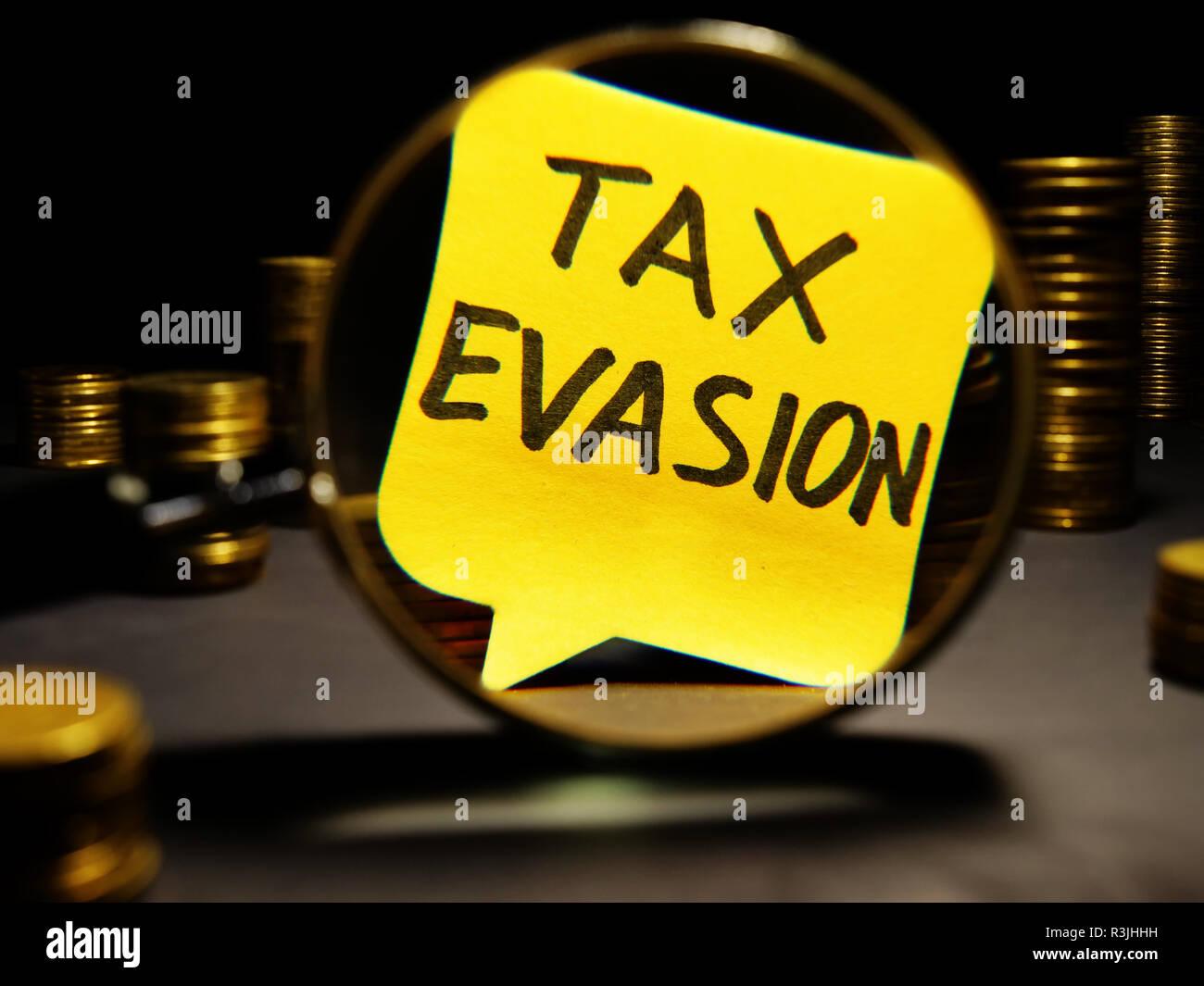 Lupa y palabras la evasión tributaria con dinero. Imagen De Stock