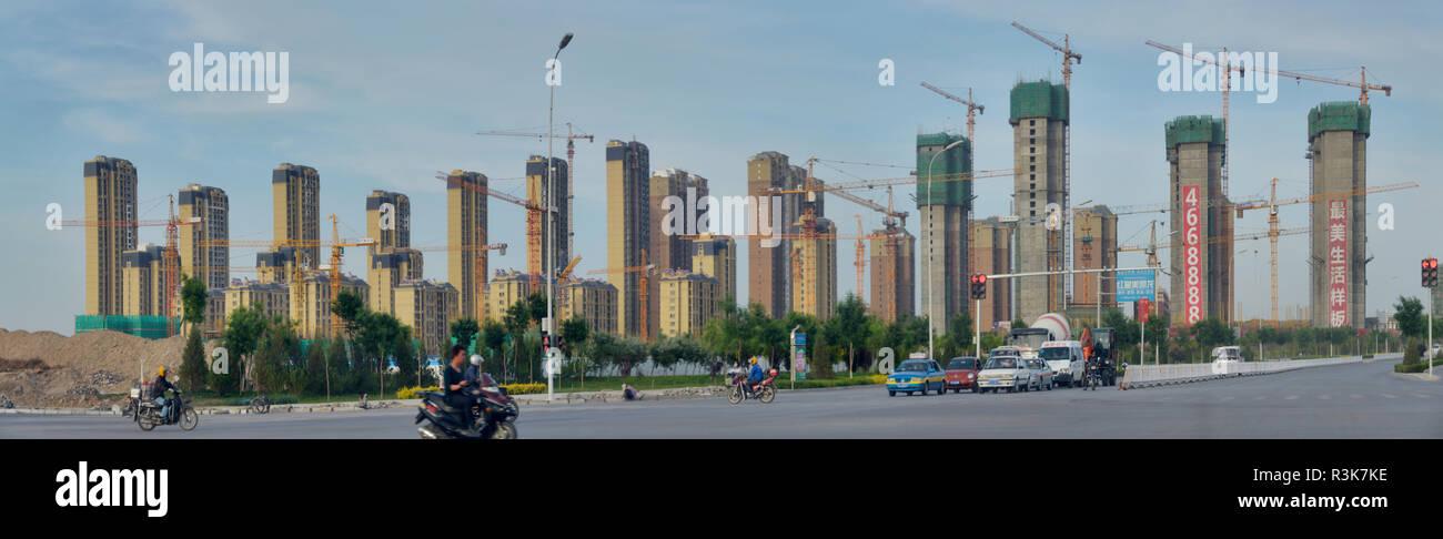 China, Ningxia, Yinchuan. Vista panorámica de un grupo de edificios altos de apartamentos en las diversas etapas de la construcción de grúas. Foto de stock