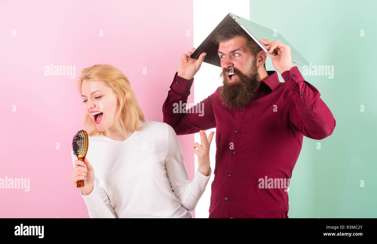Señora cantar con cepillo para el pelo como micrófono mientras el hombre  molesto escondido debajo del portátil. cc303ec1c6e5