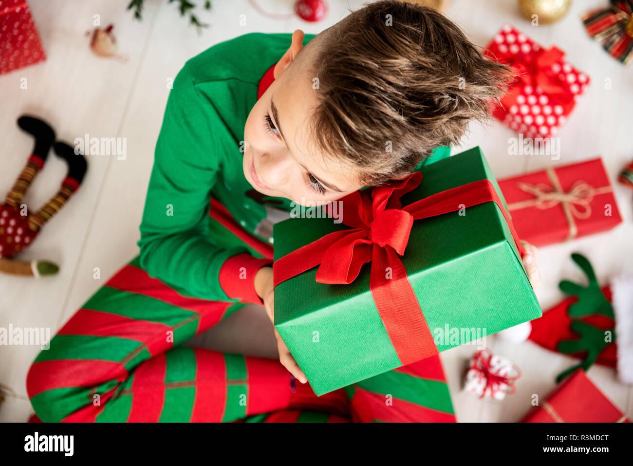 Curioso joven vestían pijamas de navidad sentados en el suelo el día de navidad, sacudir su regalo de Navidad para escuchar lo que está dentro, vista superior. Imagen De Stock