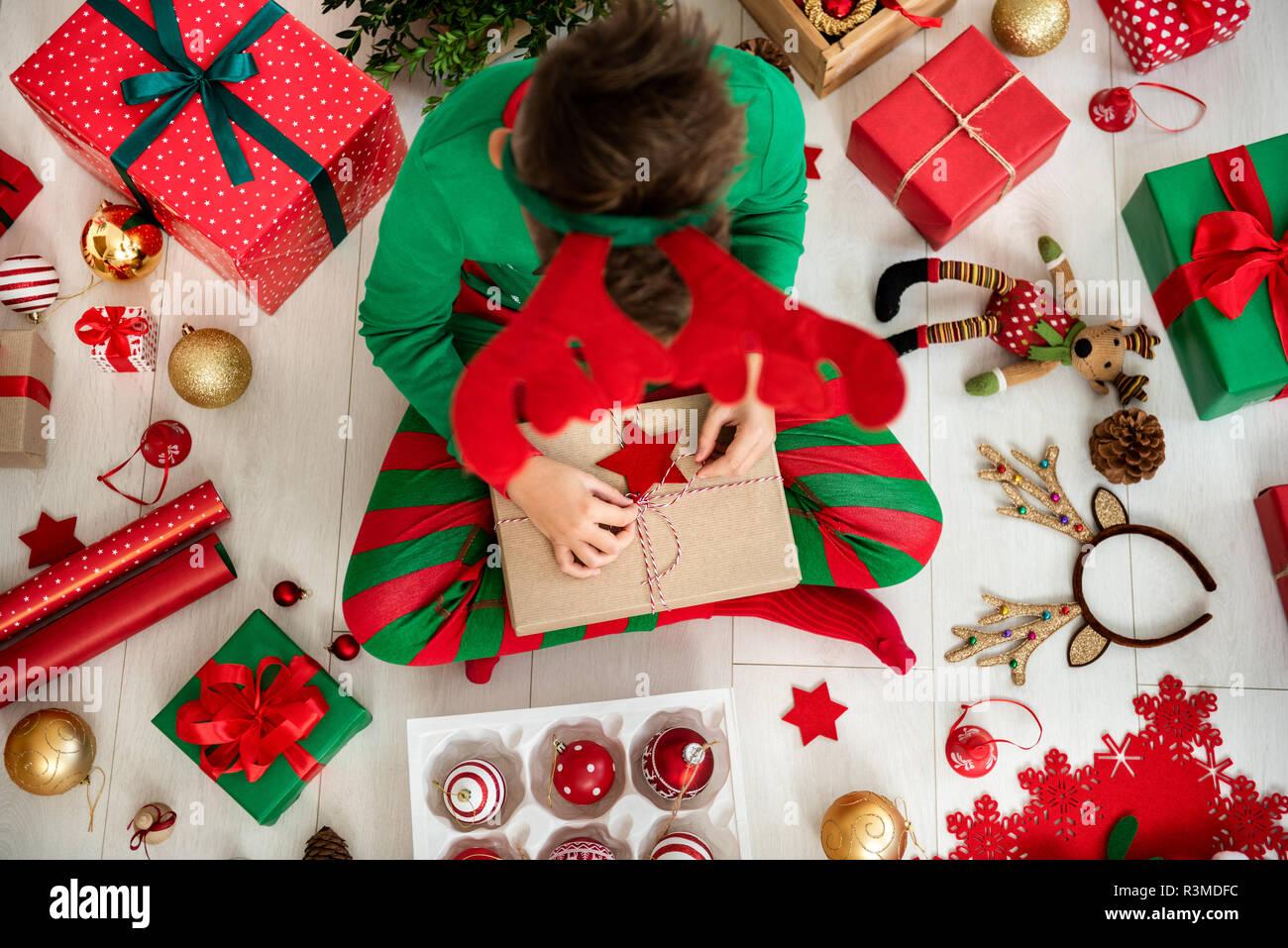 Curioso joven vestían pijamas de navidad sentados en el suelo, abriendo su regalo de navidad, vista superior. Imagen De Stock