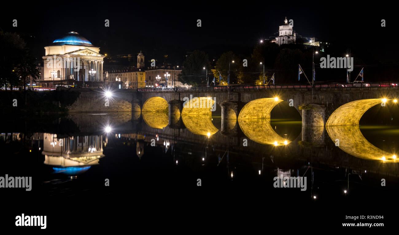 Ponte Umberto I, puente sobre el río Po, en el centro de Turín, Italia. La Iglesia de la Gran Madre puede verse sobre el puente. Fotografiado en la noche. Foto de stock