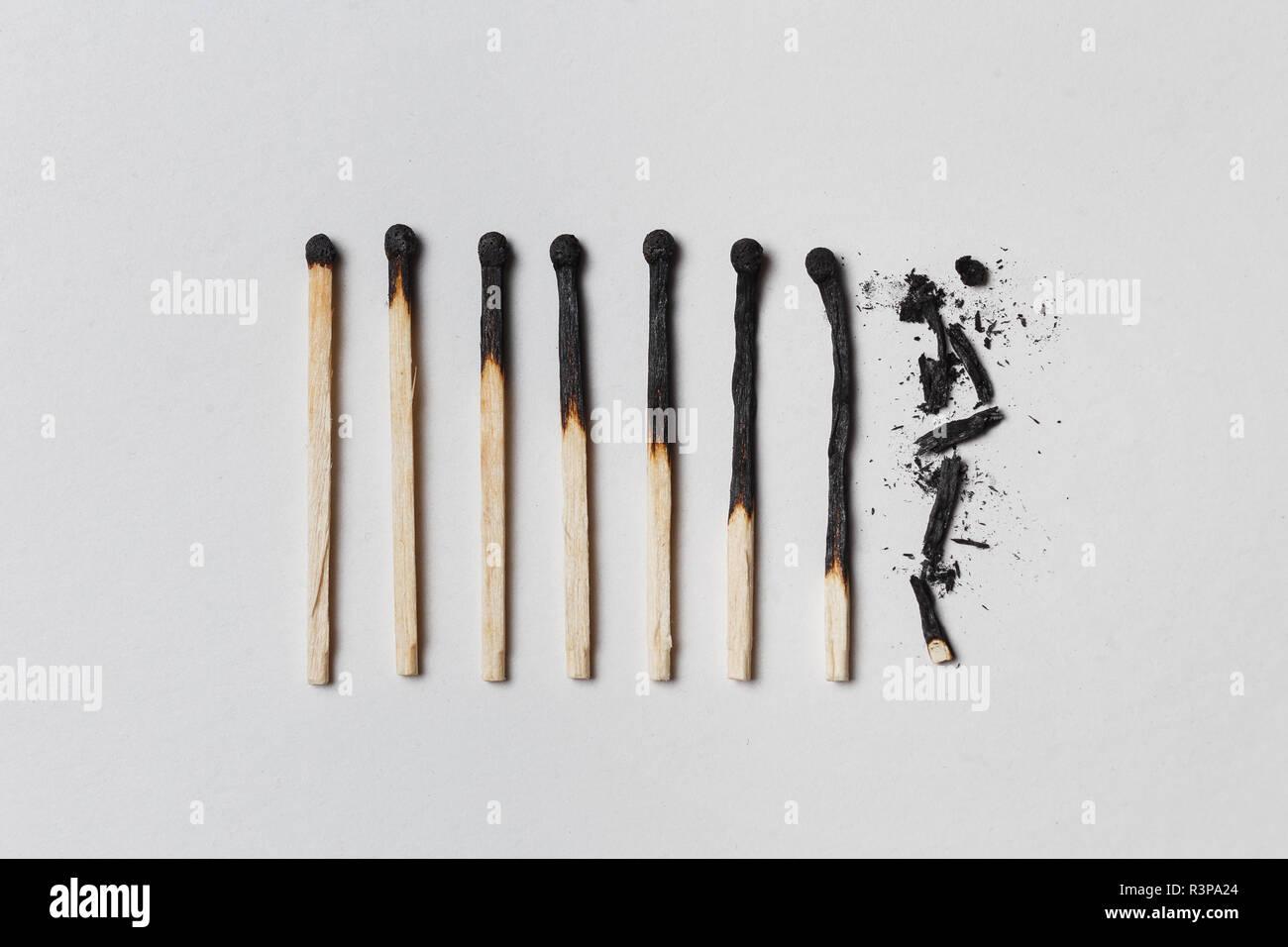 Concepto de paciencia. Una fila de fósforos quemados, de izquierda a derecha, desde casi un partido entero completamente quemado a una coincidencia en el polvo. Fondo blanco, plano laical. Foto de stock