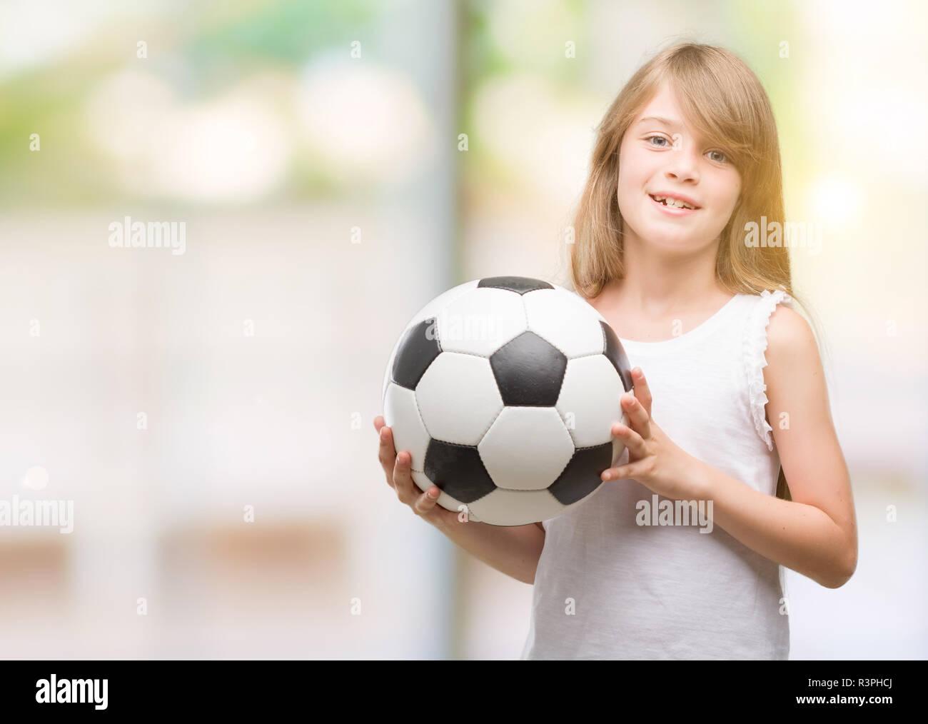 Joven rubia niño sosteniendo la bola de fútbol con una cara feliz y  sonriente permanente con e97e4d03478