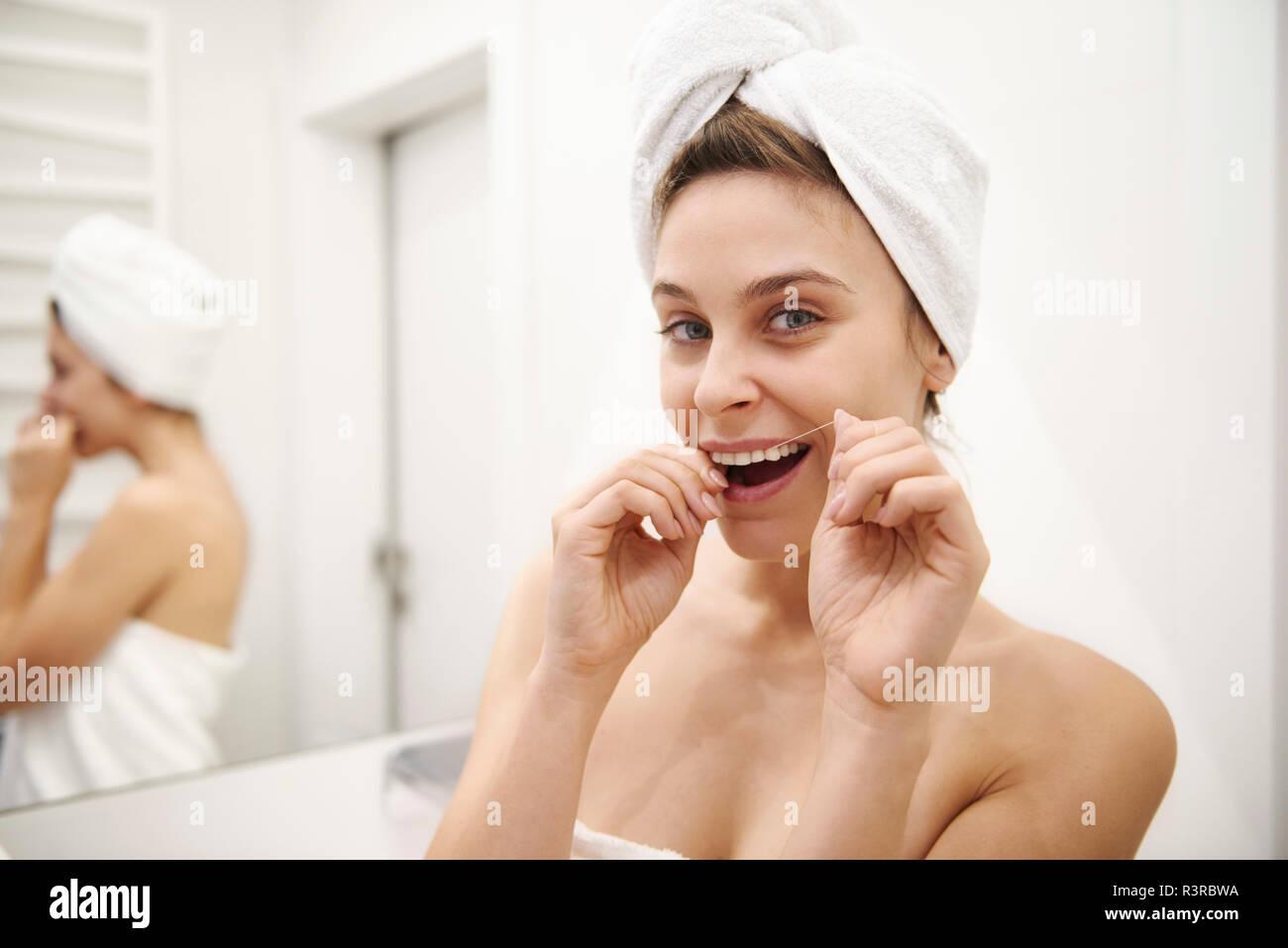 Retrato de mujer joven con hilo dental en el baño. Foto de stock