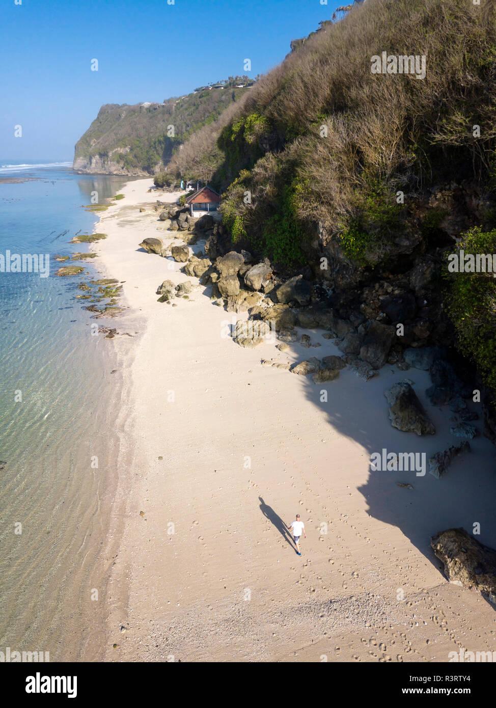 Indonesia, Bali, vista aérea del Karma Kandara playa, hombre que camina en la playa Foto de stock