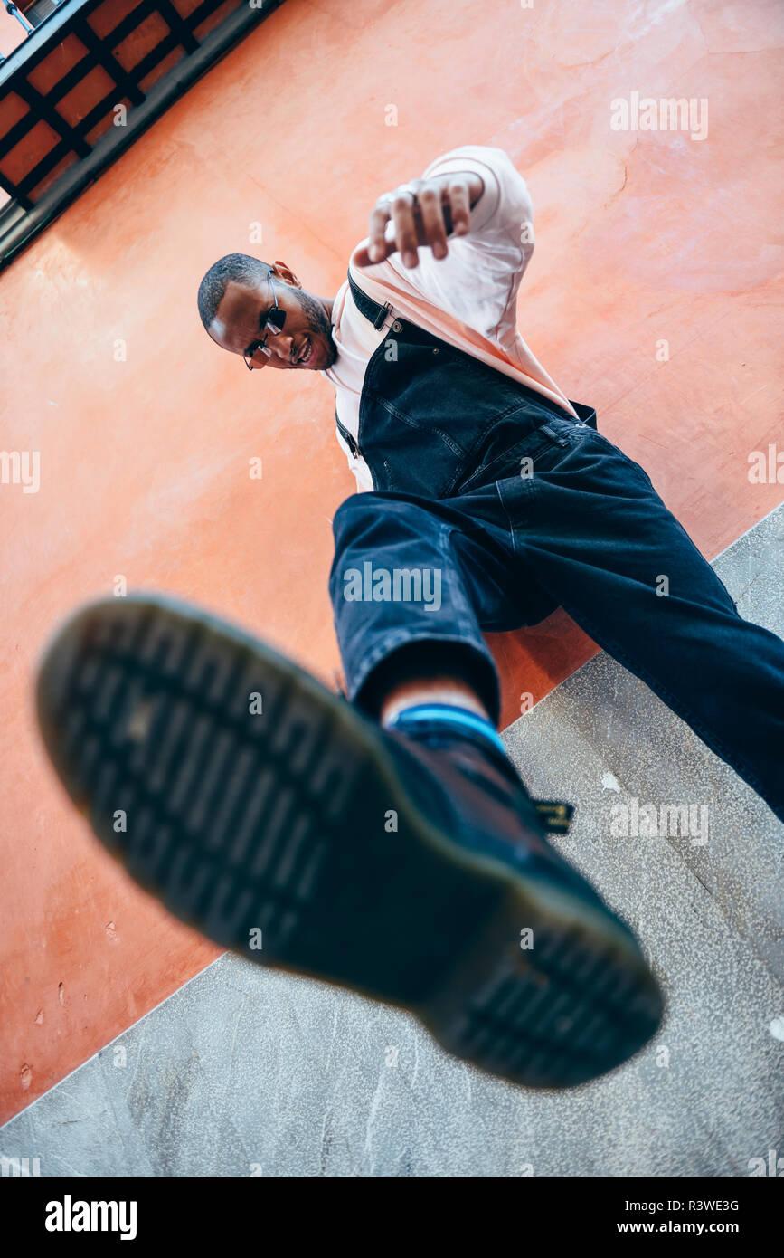 Joven negro hombre pateando hacia el suelo. Concepto de estilo de vida. Foto de stock