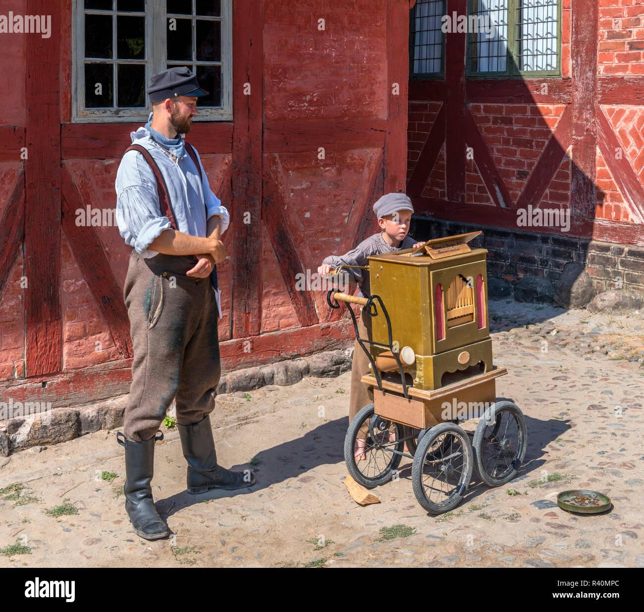 Y el hombre joven con trajes de época jugando organillo, Plaza del Mercado (Torvet), la Ciudad Vieja (Den Gamle By), un museo al aire libre en Aarhus, Dinamarca Imagen De Stock
