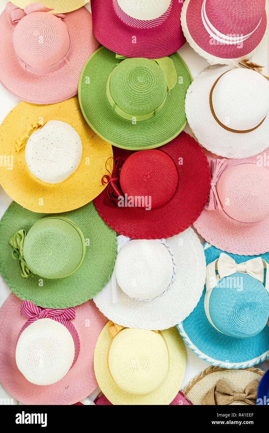 Variedad de coloridos sombreros de Paja colgado en una pared. Imagen De  Stock a0c51314bc1