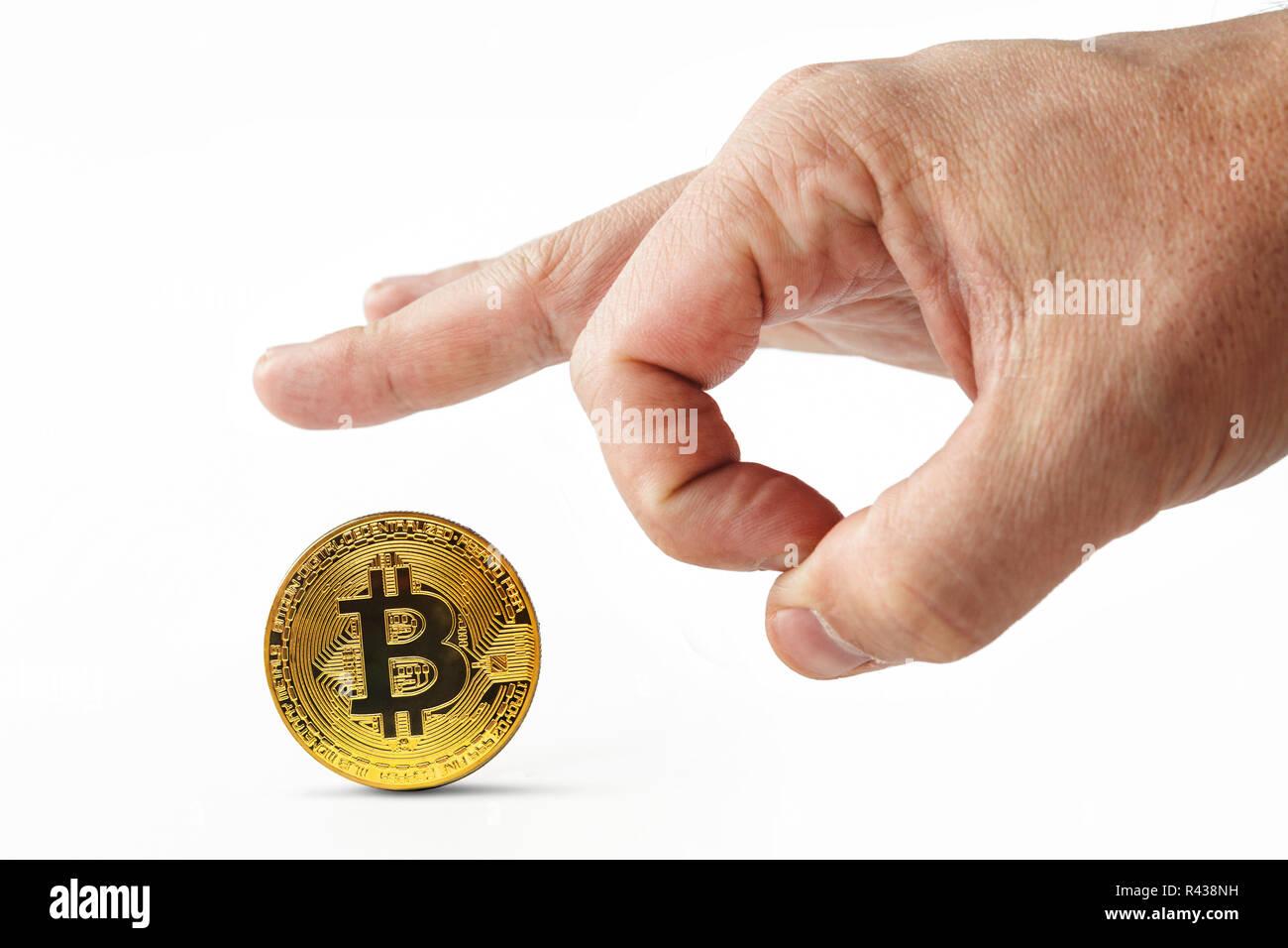 Empujar los dedos masculinos lejos bitcoin dorados sobre fondo blanco. Echando mano del hombre aislado inútil cryptocoin lejos. Crash de cryptocurrency. Se deprecia el dinero virtual. Inútil bitcoins son patadas. Foto de stock