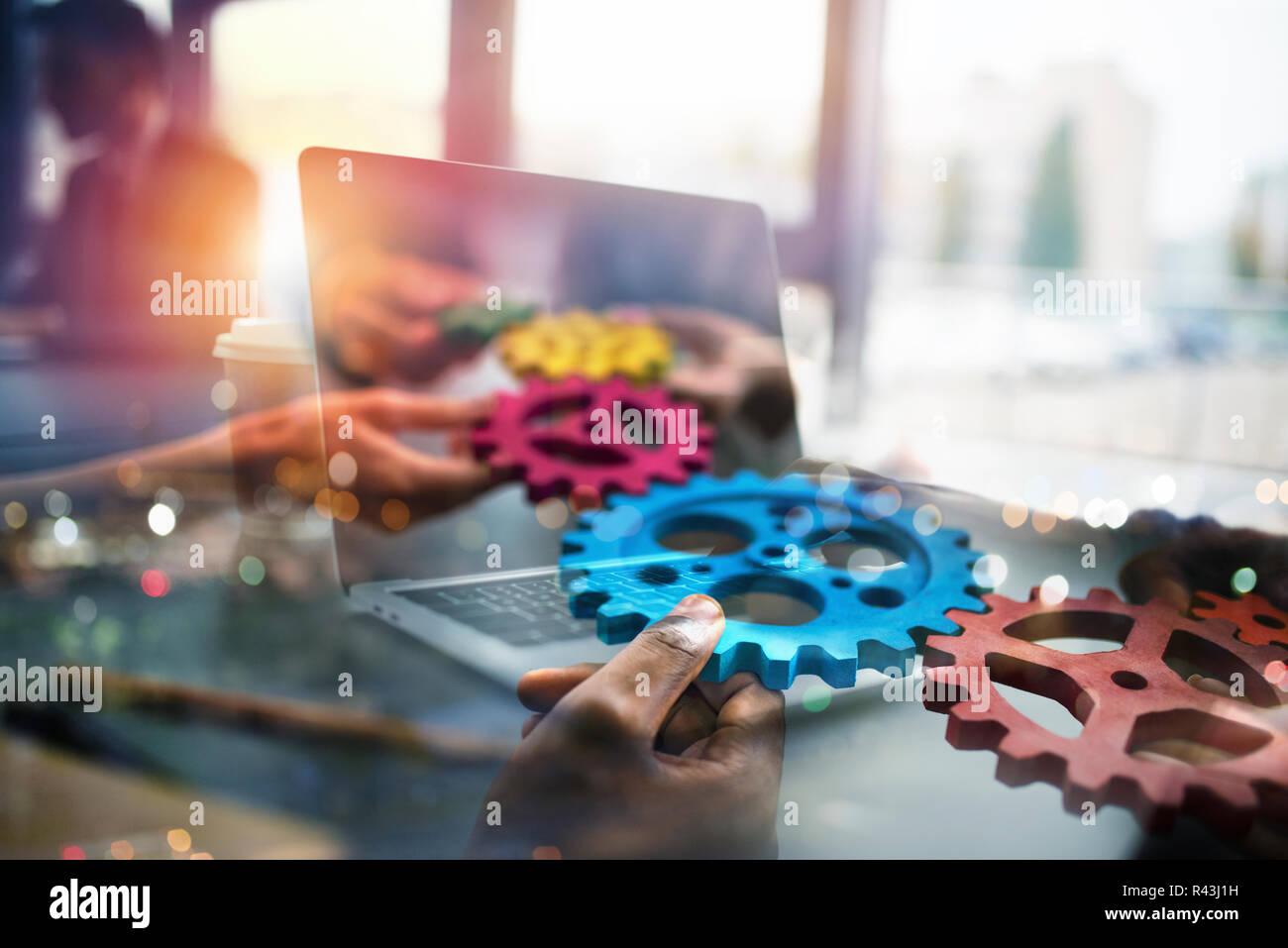 La gente de negocios con engranajes en mano que salir desde un portátil. concepto de cooperación y trabajo en equipo a distancia. Exposición doble Foto de stock