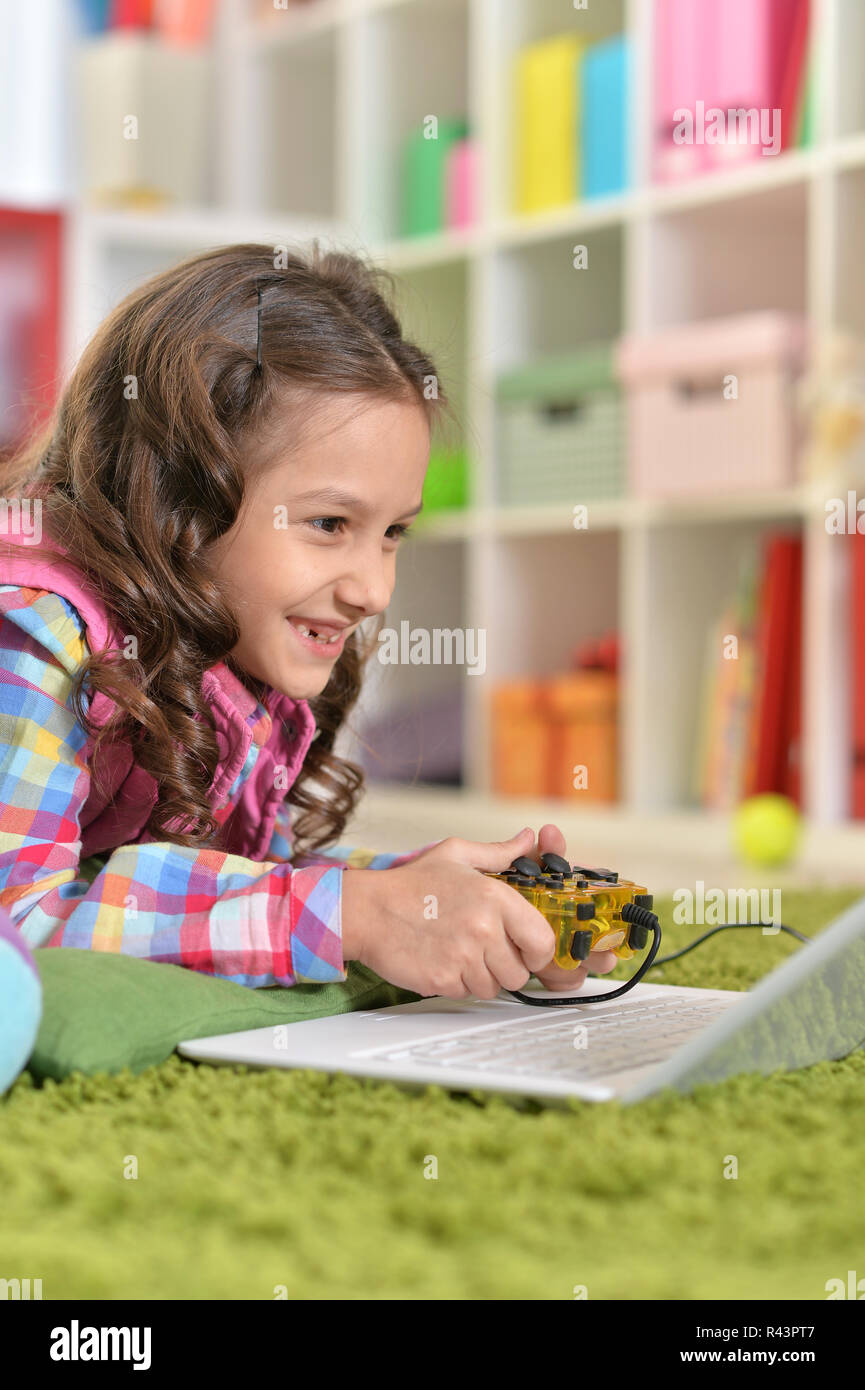 Linda niña jugando con juegos de ordenador portátil Foto de stock