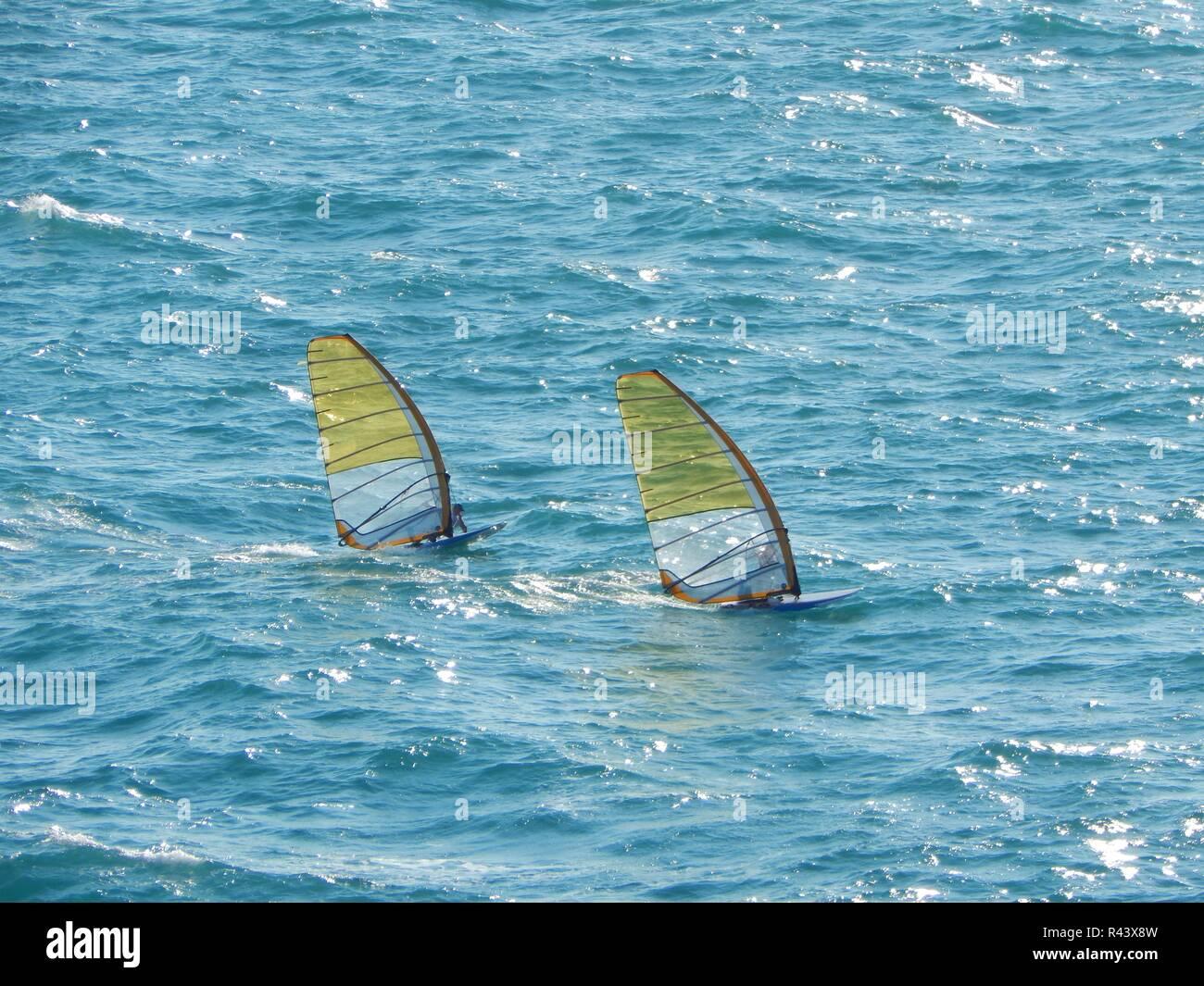 Dos windsurf ir bajo el sol deslumbrante en mar gruesa en el mar en altas velocidades Foto de stock