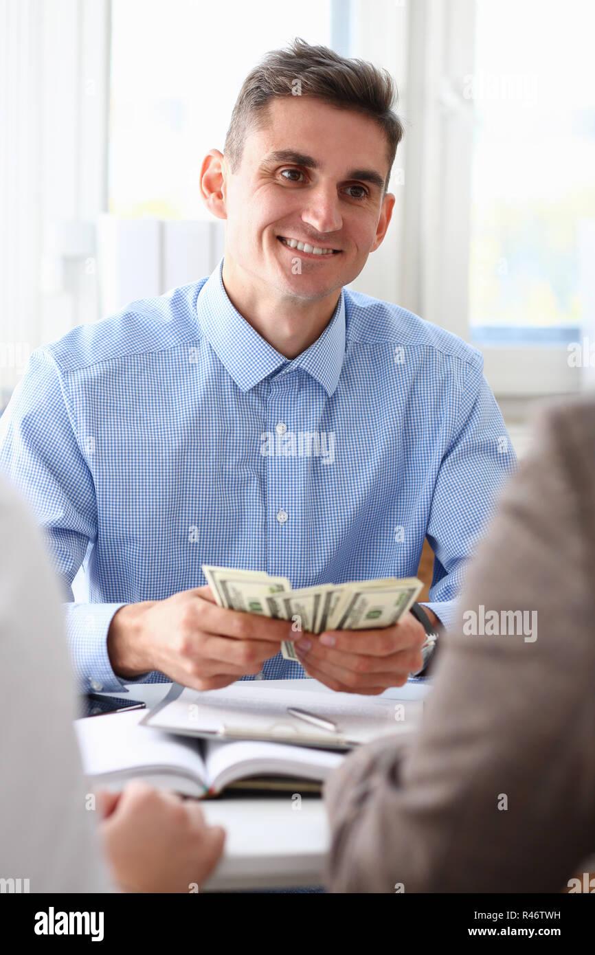 El empresario considera dólares en efectivo en la oficina Foto de stock