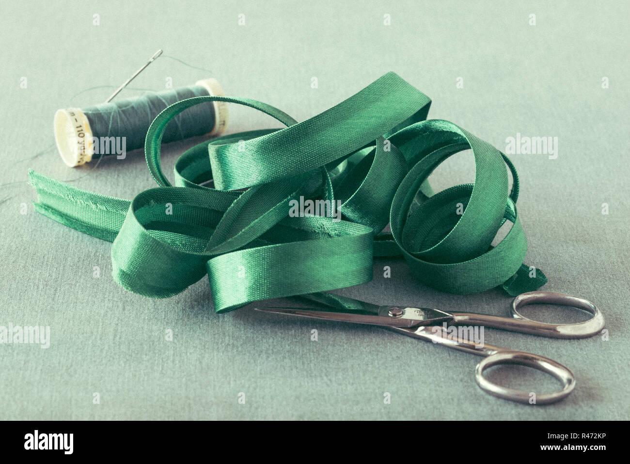 El sesgo de satén verde cerca vinculante con tijeras e hilo Foto de stock