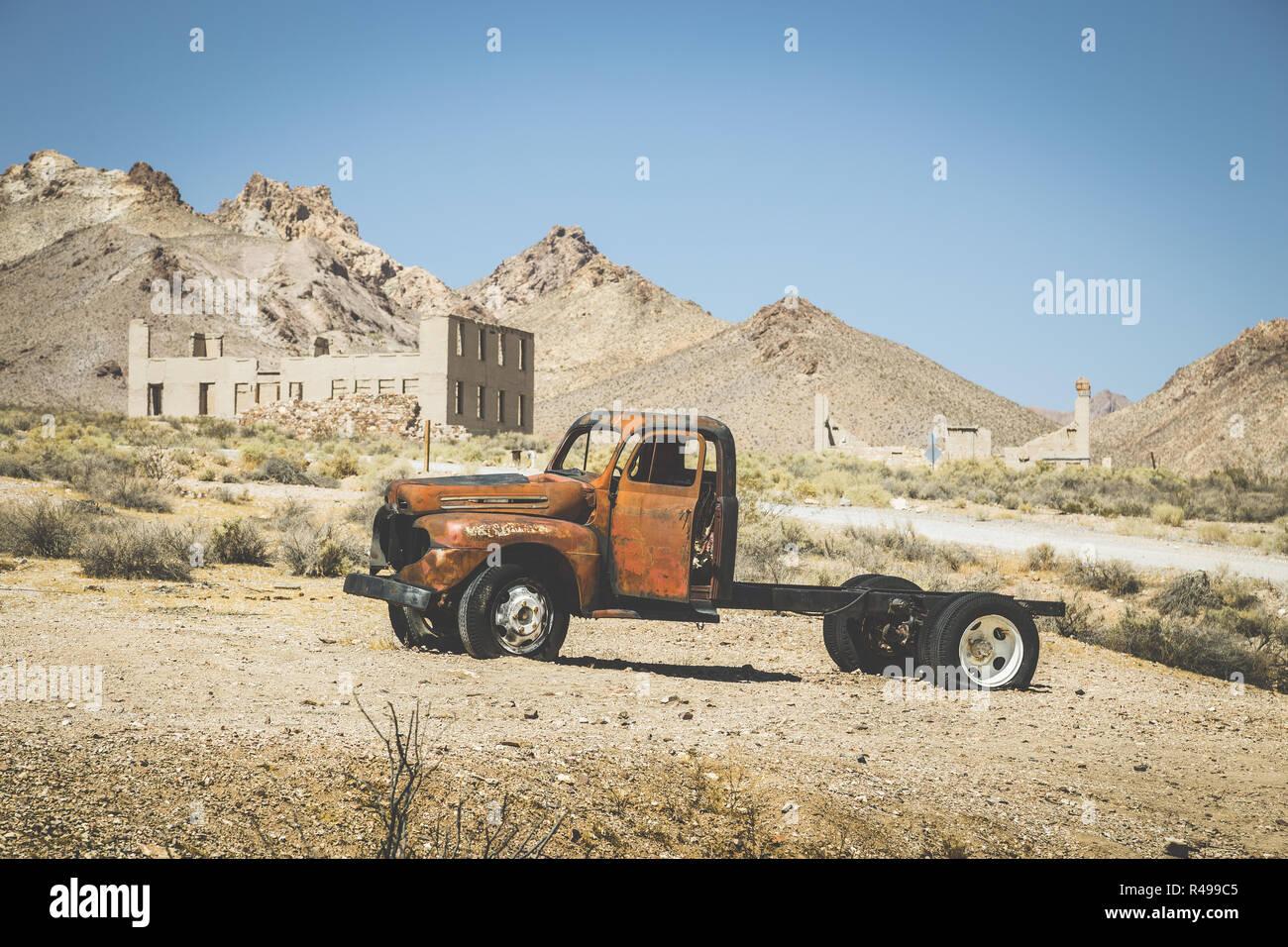 Vista clásica de una vieja camioneta oxidada de un accidente automovilístico en el desierto, en un hermoso día soleado con el cielo azul en verano con filtro de efecto vintage retro Foto de stock