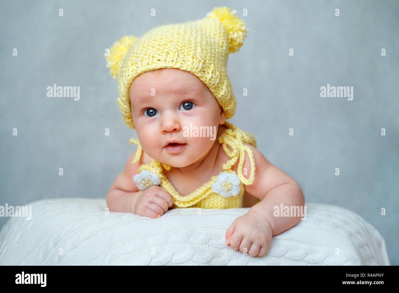 Retrato de un lindo bebé niña en tejidos bodysuit amarillo y sombrero  tumbado sobre su estómago 20bb99556c3