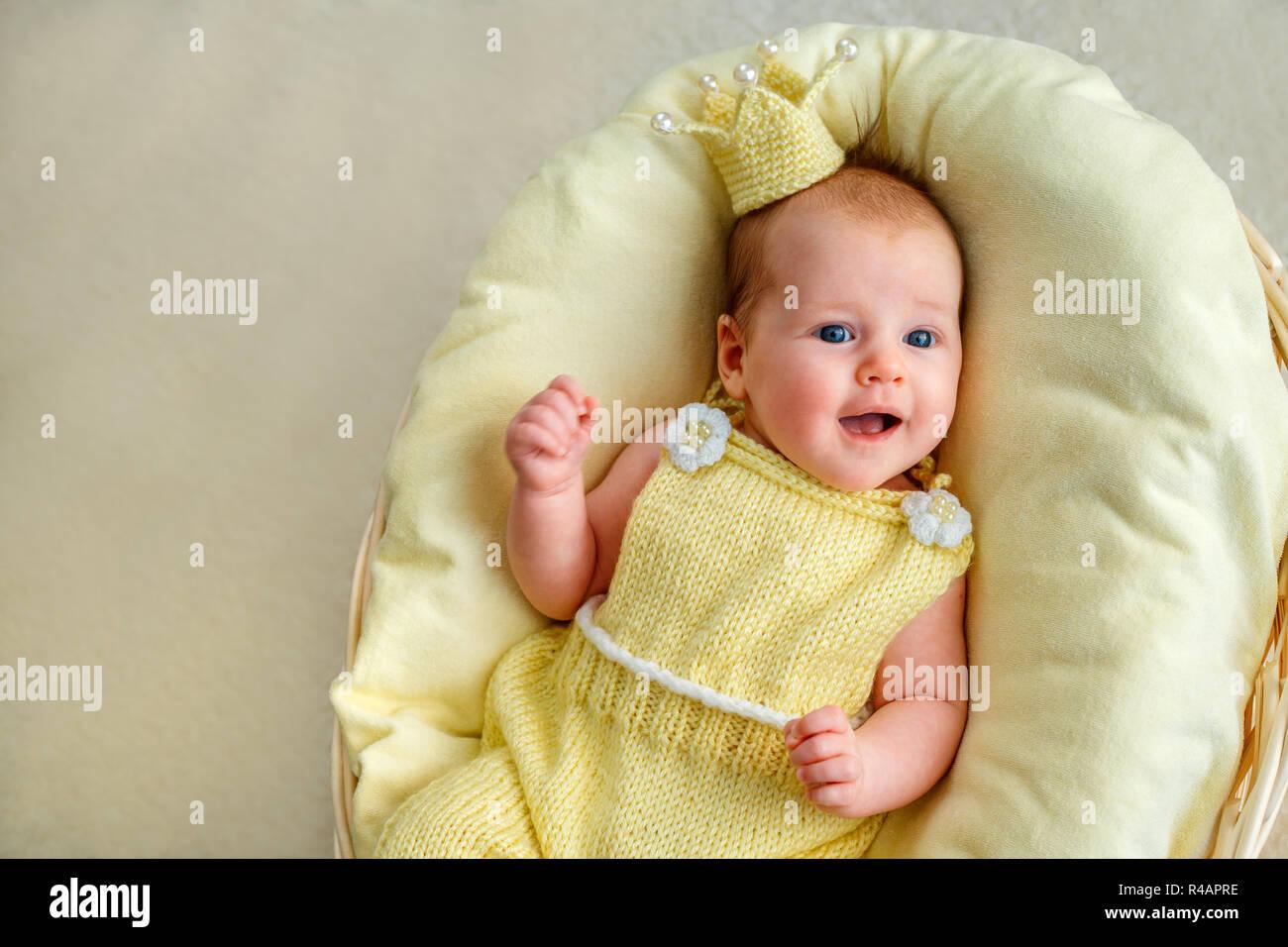Niña recién nacido recostado en una cesta con corona y amarillo bodysuit  Imagen De Stock 4232a7fc4f9