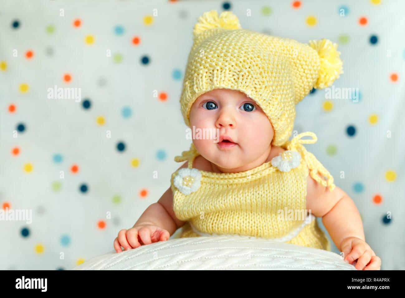 Retrato de un lindo bebé niña en tejidos bodysuit amarillo y sombrero  posando en gran bola 271892d2c48